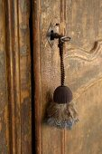 Key chain with feathers hanging from the old, battered door of country home