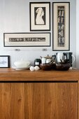 Wood with dark accessories - framed prints above contemporary, hardwood kitchen unit with pots and bowls