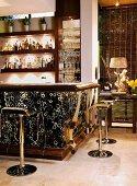 Illuminated bar clad with animal skin print and chrome bar stools