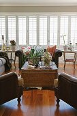 Light and bright living room with a large bank of windows, wicker table and animal skin rug
