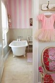 Bathroom with freestanding bath tub and pink and white striped wallpaper