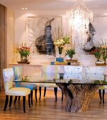 Glass table with rustic base made from tree trunk and upholstered chairs in dining room