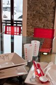 Crockery and glasses on glass table in front of rustic stone wall with snowy chalet roofs in background