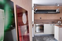 View into modern kitchen with grey stone floor tiles and wooden splashback