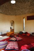 Colourful, Indian cushions on red rug in meditation room with domed, concrete ceiling