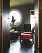 View through door into interior in dark shades with red armchair and sculpture in round window