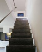Simple, dark, steel plate staircase with handrail in open-plan interior