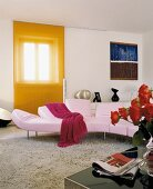 Pink sofa in modern living room in front of window with orange, transparent, sliding panel curtain