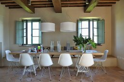 Dining area with white shell chairs and designer pendant lamps in renovated country house