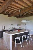 Contemporary kitchen counter with designer bar stools in open-plan kitchen of renovated country house