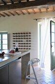 Kitchen counter with designer bar stool in front of open terrace door