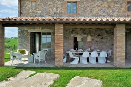 White terrace furniture beneath porch of Mediterranean country house with stone facade