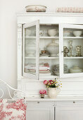 White, vintage dresser with open doors and view of crockery