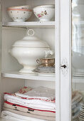 Table linen and crockery in glass-fronted cabinet with open door