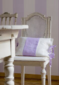Old French chairs around wooden table in Gustavian style in front of purple and white striped wall