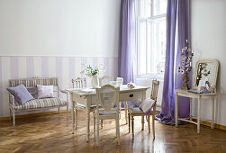 Old French chairs around wooden table in Gustavian style and bench against purple and white striped wall
