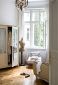 Wardrobe, tailors' dummy and old iron armchair in front of open window in bedroom of period apartment
