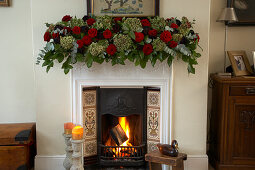 English Christmas decoration: sumptuous garland of roses on mantelpiece above roaring fire