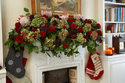 Opulent garland of roses, hydrangeas and protea flowers as Christmas decoration on traditional English mantelpiece