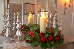 Lit candles in arrangement of roses and stylised metal fir trees in front of hall mirror
