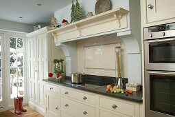 Cream country house kitchen in simple Shaker style with modern stainless steel appliances and masonry extractor hood