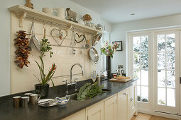 Shaker-style, cream country house kitchen with romantic ornaments over dark stone-effect worksurface