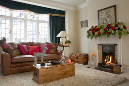 Classic, festively decorated living room; stylised stag on trunk-style coffee table and garland of roses on mantelpiece