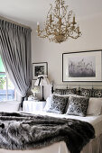 White, country house bedroom with grey accessories and gilt chandelier