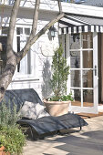 Two modern sun loungers on wooden deck in front of wooden facade of renovated country house; open terrace door with striped awning