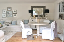 White living room in romantic, elegant country house style with loose-covered chairs at round dining table next to serving hatch leading to kitchen