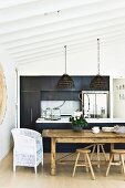 White wicker chair and rustic stools at dining table in front of open-plan, black kitchen