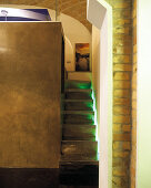 Narrow stairs with indirect lighting leading to gallery on cubic room-in-room installation below historic brick vault