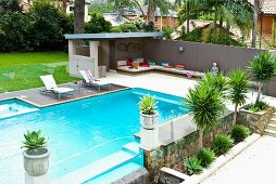 Modern pool area with palms and terrace with patio furniture