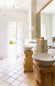 Zwei runde Waschbecken auf frei stehenden Podesten im römischen Stil im hellen Bad mit Zugang zum Gartenbereich