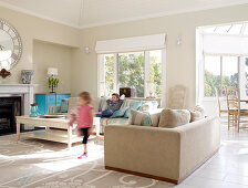 Children playing in bright, spacious lounge area with pastel blue, vintage chest of drawers