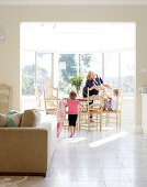Mother and children in sunny dining room with panoramic windows