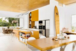 Dining table in front of counter in open-plan kitchen of contemporary house