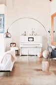 Bauhaus-style arc lamp in front of white antique piano in corner of living room