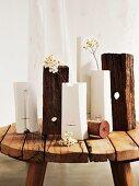 Verschiedene Vasen in Weiss und Holzstücke auf rustikalem Schemel