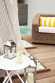 Lantern on modern side table and comfortable wicker armchair on modern wooden terrace