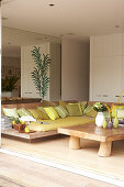 Lounge area with cushions on low wooden frames and rustic coffee table in modern living room