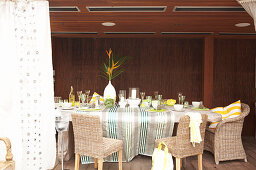 Table with a tablecloth in front of a dark wooden wall on a veranda