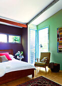 A double bed in a colourful bedroom under a sloping roof