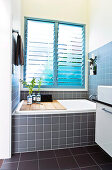 A built-in bath under a large window with blinds with a wooden shelf and a vase of flowers