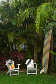 White garden chairs next to a surfboard in the corner of a garden with exotic trees and plants