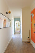 Long hallway with wooden floor and artworks on walls