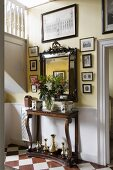 Bouquet of lilies on antique console table, mirror and old photos and drawings in entrance hall of English country house