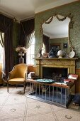Grand room with open fireplace and half-height fender seat next to antique chair with yellow fabric upholstery