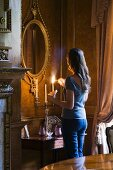 Atmospheric ambiance - woman lighting candles in front of antique, oval mirror with gilt frame in corner of grand living room
