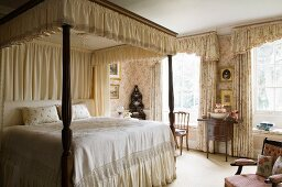 Bedroom in old English style with canopy and curtains in sumptuous fabrics